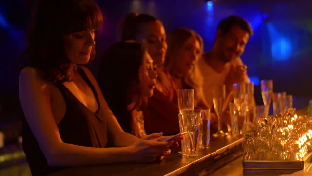 ls slo mo girl checking smartphone in nightclub - drink stock videos & royalty-free footage