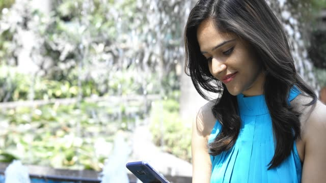 girl checking social media feed using smartphone - indian ethnicity stock videos & royalty-free footage