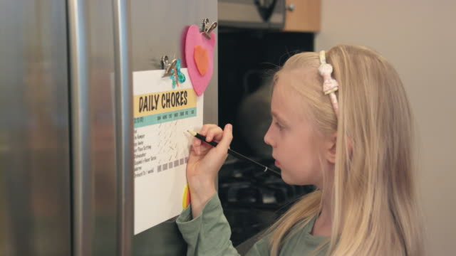 girl checks off chores from list - responsibility stock videos & royalty-free footage