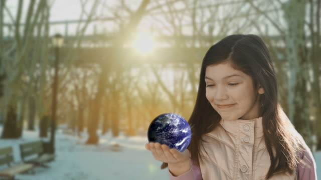 Girl child holding rotating globe earth in her hand
