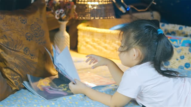 girl child reading kids book in a tent - storytelling stock videos and b-roll footage