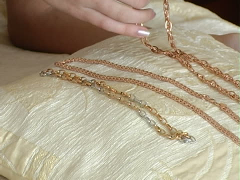 stockvideo's en b-roll-footage met girl chooses a gold chain - ketting