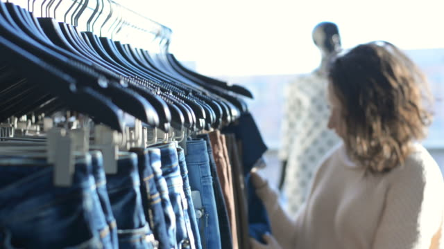 girl chooses clothes in shop - jeans stock videos & royalty-free footage