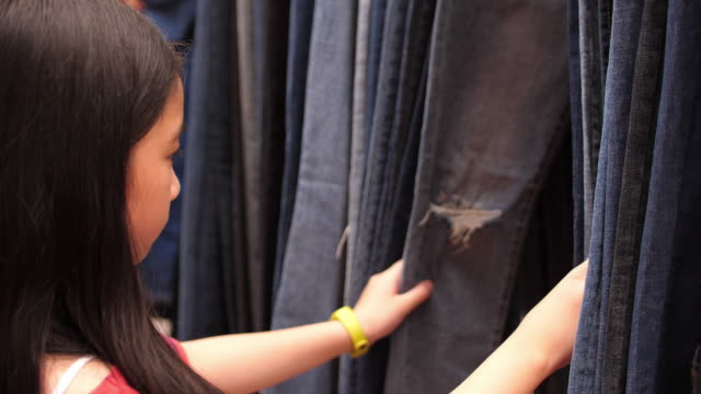 Girl choosing jeans in shop