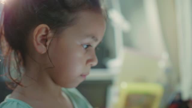 vídeos y material grabado en eventos de stock de una niña (7-8 años) eligiendo el lápiz y hacer la tarea en la mesa en la sala de estar - instrumento de escribir con tinta