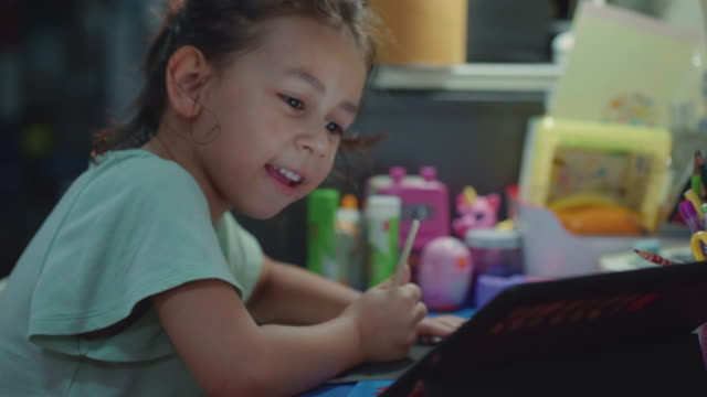 a girl (7-8 years) choosing pencil and doing homework on table in living room - 6 7 years stock videos & royalty-free footage