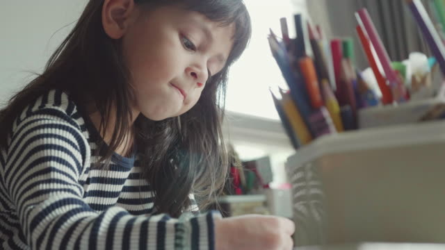 a girl (5-7) choosing pencil and doing homework on table in living room - studio camera video stock e b–roll
