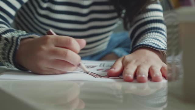 vidéos et rushes de une fille (5-7) choisir le crayon et faire leurs devoirs sur table dans le salon - gribouillage