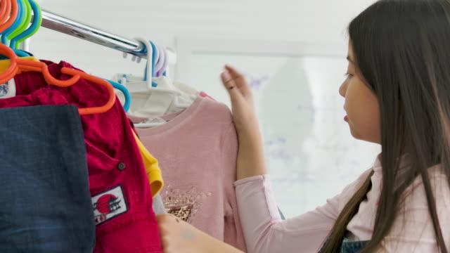 ragazza che sceglie l'acquisto di vestiti. - abbigliamento video stock e b–roll
