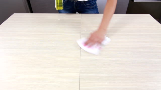 Girl cleaning and wiping table in kitchen