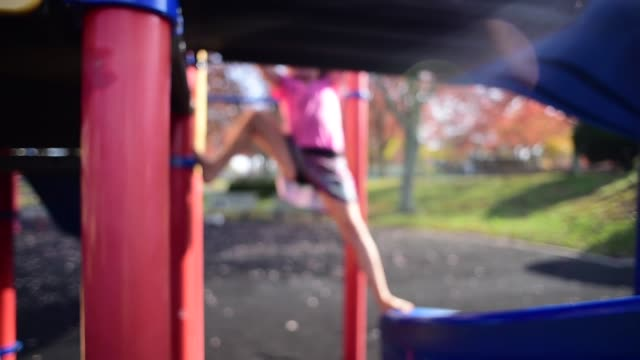 vídeos de stock, filmes e b-roll de a girl climbing a jungle gym at the park. - jungle gym