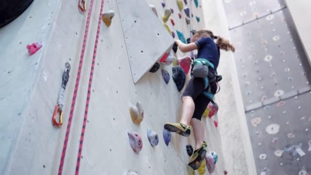 vídeos y material grabado en eventos de stock de chica escalando en la pared de escalada - escalada libre
