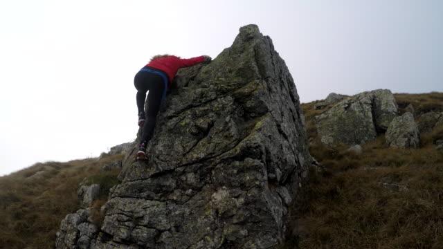 stockvideo's en b-roll-footage met meisje klimmen op de rotsen in de bergen 4k - vrij klimmen