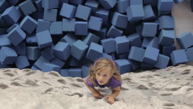 ws girl climbing rock wall and falling onto foam blocks / vancouver, british columbia, canada - kletterwand kletterausrüstung stock-videos und b-roll-filmmaterial