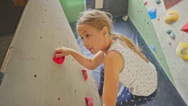 flicka klättra upp en vägg i klätt ring gym - klättervägg bildbanksvideor och videomaterial från bakom kulisserna