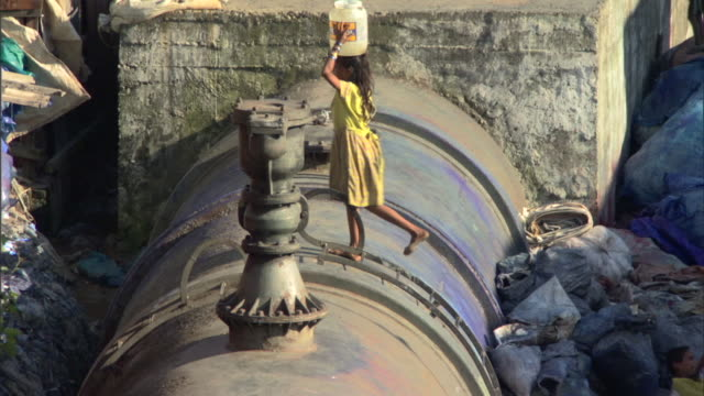 stockvideo's en b-roll-footage met ms td pan ha girl climbing water pipe and carrying bucket of water on head, mumbai, maharashtra, india - sloppenwijk