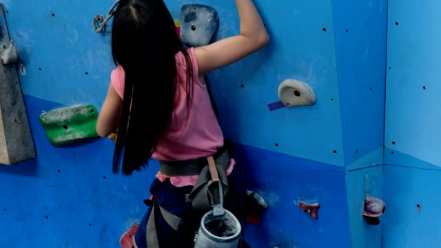 girl climbs the climbing wall in the climbing shoes and body harness - climbing wall stock videos & royalty-free footage