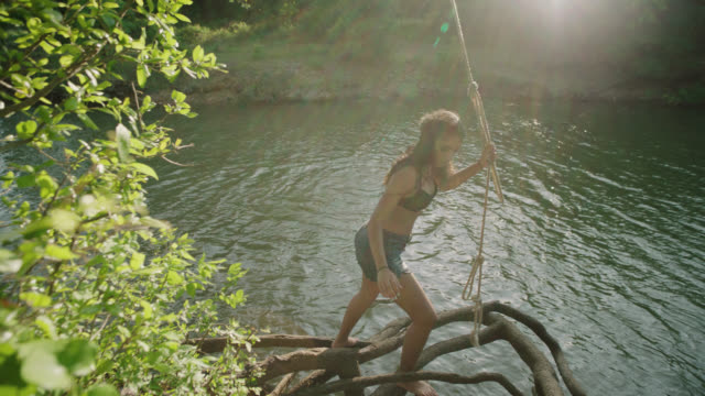 slo mo. girl climbs up tree roots to riverbank with rope swing. - rope swing stock videos & royalty-free footage
