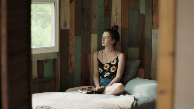 WS SLO MO. Girl closes her eyes and daydreams in rustic treehouse bedroom.