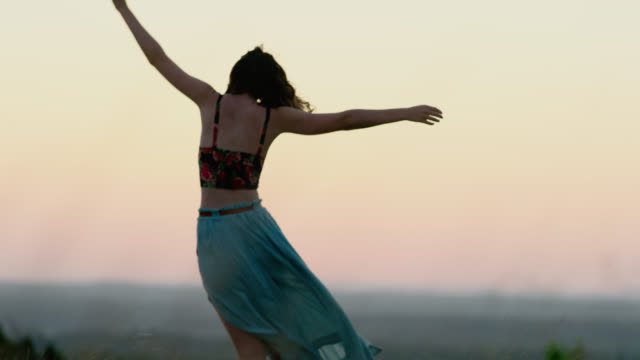 WS SLO MO. Girl comes into focus walking through field in flowing dress at magic hour.