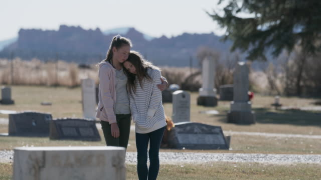 girl comforting sister near gravestone in cemetery / bicknell, utah, united states - grief stock videos & royalty-free footage