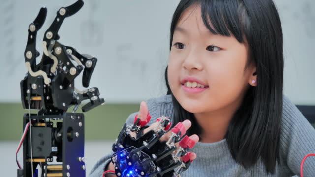 vídeos y material grabado en eventos de stock de niña construye y programa en la computadora y la construcción de un brazo robot como un proyecto de ciencias escolares. ella está muy satisfecha con su trabajo. educación, tecnología, trabajo en equipo, ciencia y concepto de personas. temas de educaci - robótica