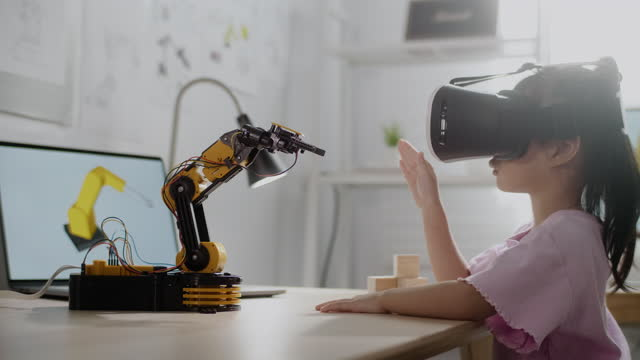 girl control robot arm on vr glasses, getting a lesson in robotics in high school - machine learning stock videos & royalty-free footage
