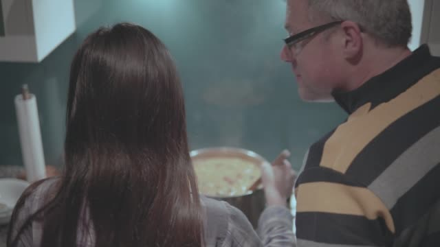 vídeos y material grabado en eventos de stock de chica cocinando en una estufa con su padre - padre soltero