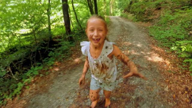 pov少女は森の小道で実行されているカメラをキャッチしようとしながら笑いながら泥に覆われて - 田舎道点の映像素材/bロール