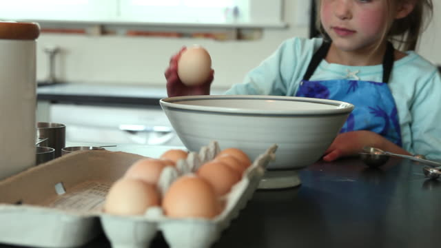stockvideo's en b-roll-footage met cu focusing girl (6-7) cracking eggs into ceramic bowl, yarmouth, maine, usa - 6 7 jaar