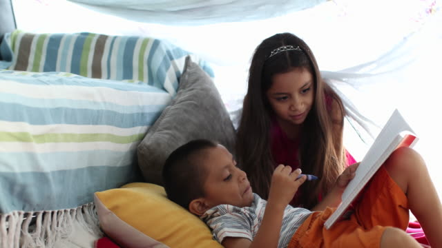 vidéos et rushes de girl crawls in to home made tent to join young brother. - oreiller