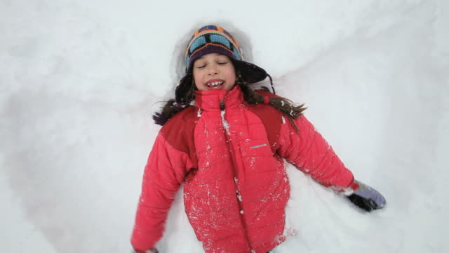 ms zi zo girl creating snow angel during snowstorm / yarmouth, maine, usa - 仰向きに寝る点の映像素材/bロール