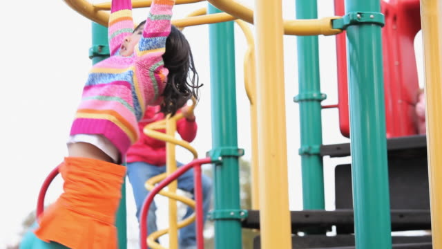 ms la pan girl (6-7) crossing on monkey bars on playground / richmond, virginia, usa - jungle gym stock videos and b-roll footage