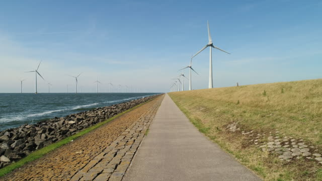 girl cycling along wind turbines - embankment stock videos and b-roll footage
