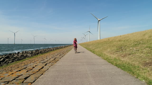 vídeos de stock, filmes e b-roll de girl cycling along wind turbines - 30 segundos ou mais