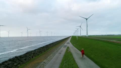 girl cycling - 風力発電点の映像素材/bロール