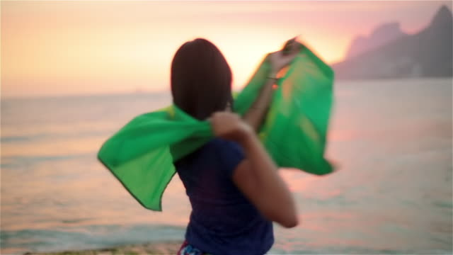 girl dances and twirls brazilian flag in the wind on ipanema beach at sunset - brazilian culture stock videos & royalty-free footage