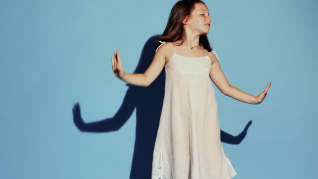 MS Girl (4-5) dancing against blue background / New York City, New York, USA