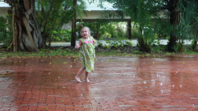 ws girl (2-3) dancing in rain and splashing in puddle / lamy, new mexico, usa - pioggia video stock e b–roll