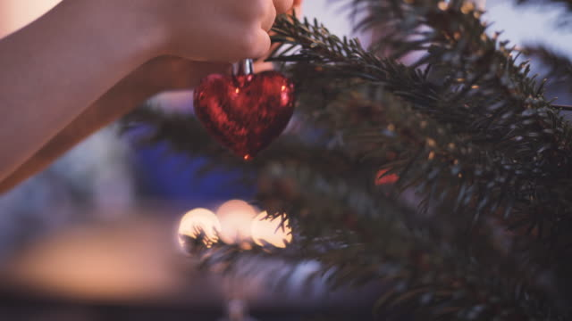 stockvideo's en b-roll-footage met girl decorating christmas tree at home - kerstboom versieren