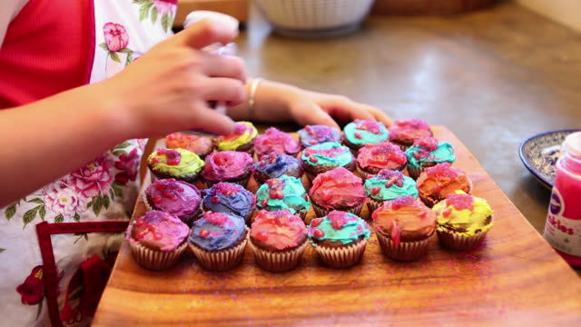 MS TU Girl decorating cupcakes in kitchen / Lamy, New Mexico, United States