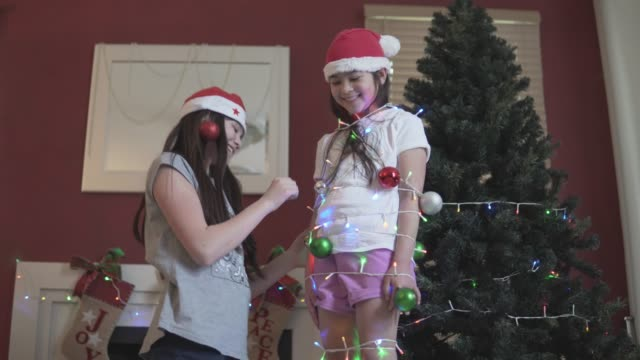 girl decorating her younger sister with christmas ornaments - new zealand culture stock videos and b-roll footage
