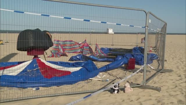 girl dies after being thrown from exploding bouncy castle; england: norfolk: gorleston: ext various of deflated bouncy castle behind fences blue... - itv weekend late news点の映像素材/bロール