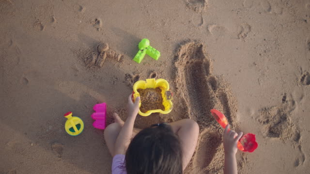 girl digging and scooping sand on the beach - castle stock videos & royalty-free footage