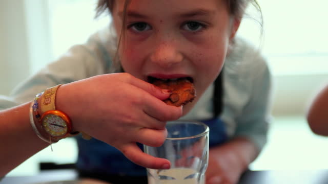 stockvideo's en b-roll-footage met cu td focusing girl (6-7) dipping chocolate chip cookie in milk, yarmouth, maine, usa - zoet voedsel