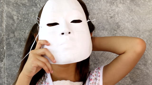 girl disguise with mask ,playing with mask - young girls stripping stock videos and b-roll footage