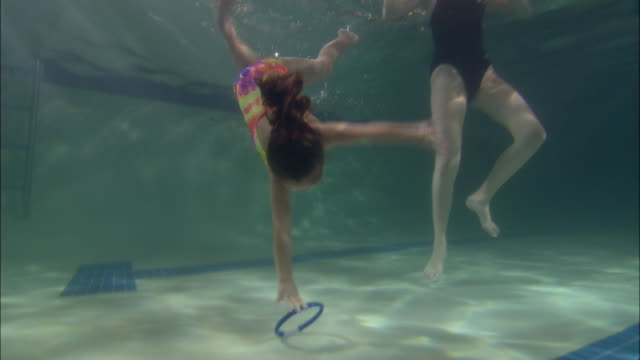 LA WS Girl diving to bottom of pool to retrieve plastic ring and swimming back to woman standing in pool / Riverhead, New York, USA
