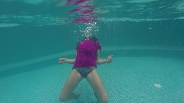 girl does back flip in pool underwater - バク転点の映像素材/bロール