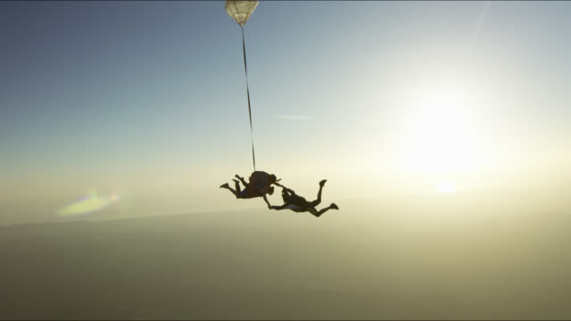 girl does tandem skydive at sunset - tandem stock videos & royalty-free footage