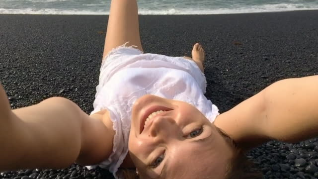 Girl doing a video selfie laying upside down on the volcanic beach of Lanzarote smiling and enjoying the beach alone during a travel vacations, recorded with smartphone in slow motion.
